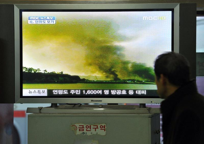 A South Korean man watches a public television screen broadcasting a report about North Korea's firing over the South Korean border island of Yeonpyeong near the tense Yellow Sea border, 11/23/2010