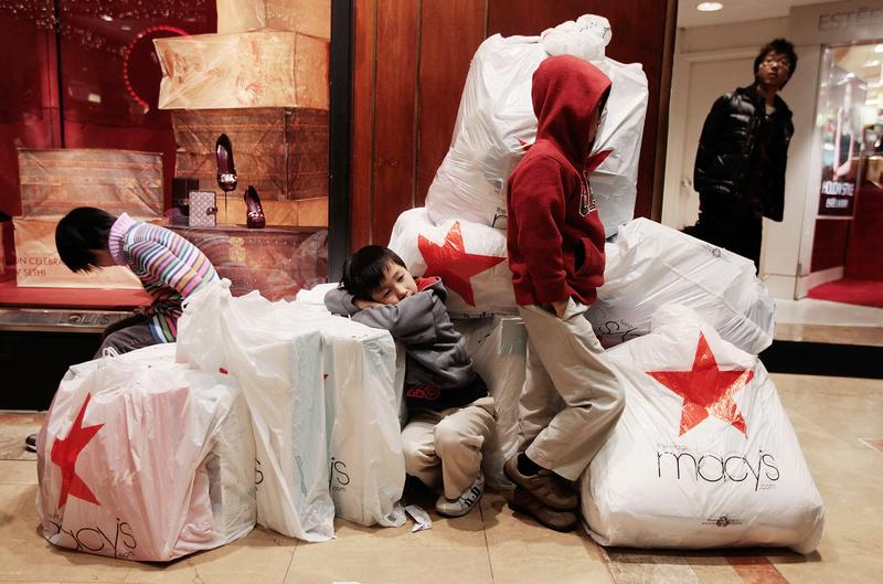 5460de63b Children wait with shopping bags inside Macy s department store on  Black  Friday.