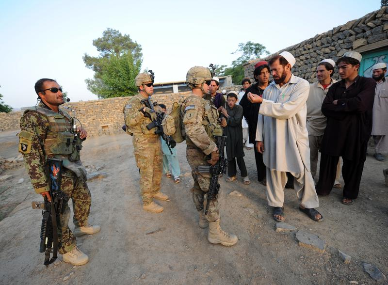 US soldiers of the Viper Company (Bravo), 1-26 Infantry, talk to Afghan men as they conduct a house to house search operation for weapons in the Khost province of eastern Afghanistan on June 19, 2011.