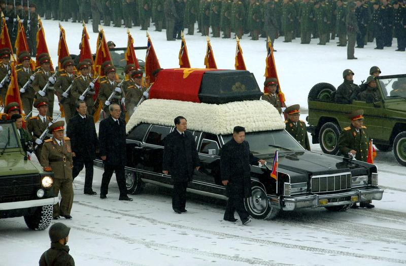 Kim Jong-un (center R) besides the convoy carrying the body of his father and late leader Kim Jong-il at Kumsusan Memorial Palace in Pyongyang on December 28.