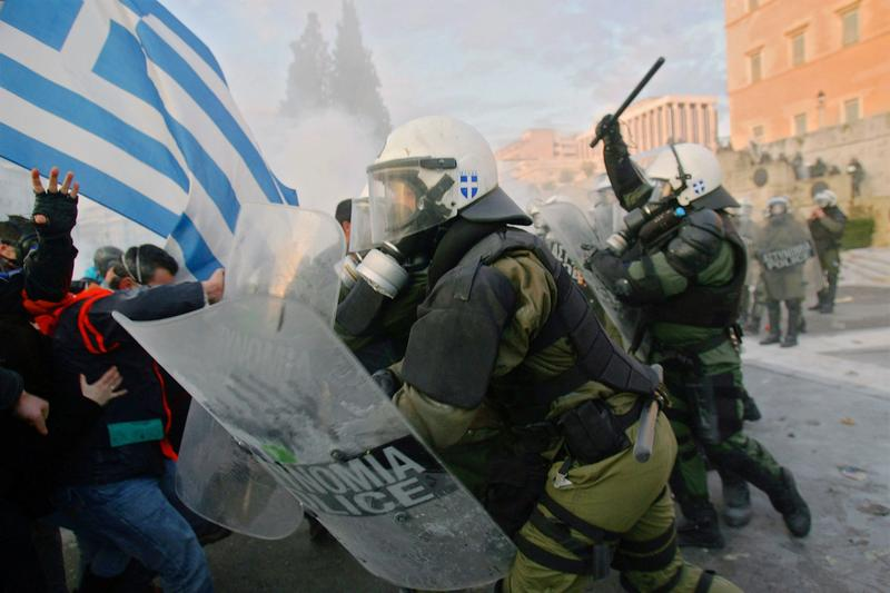 People clash with police during a demonstration against the new austerity measures in Athens, Greece.