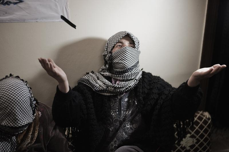 A Syrian woman gestures as she works on flags to be used in a demonstration at a workshop in Qusayr.