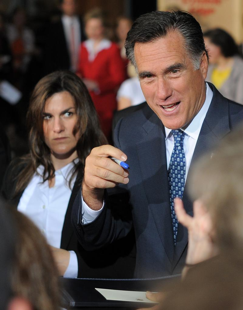 Republican presidential candidate Mitt Romney (left) signs autographs for supporters during a campaign event in Chantilly, Virginia, on May 2, 2012.
