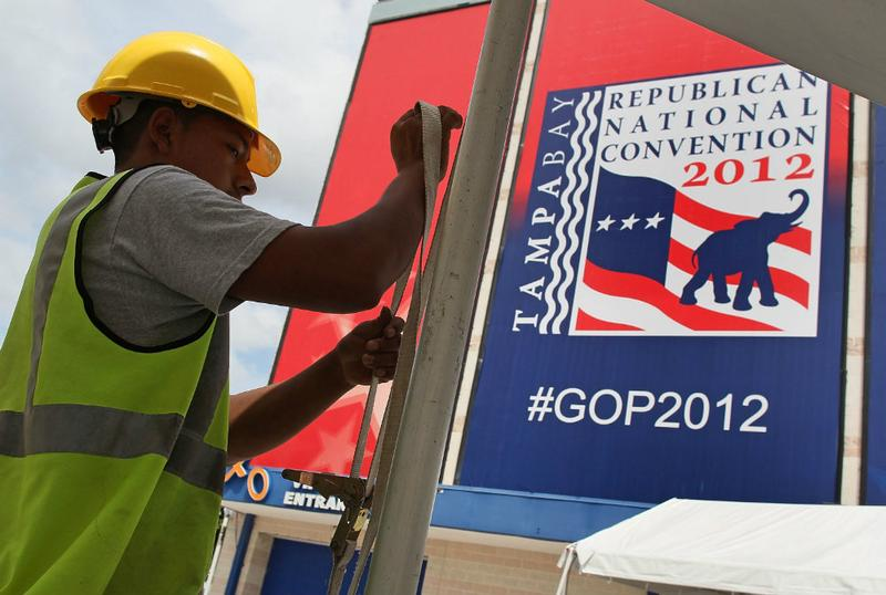 A worker secures a tent for the Republican National Convention at Tampa Bay Times Forum as the region prepares for Tropical Storm Isaac.