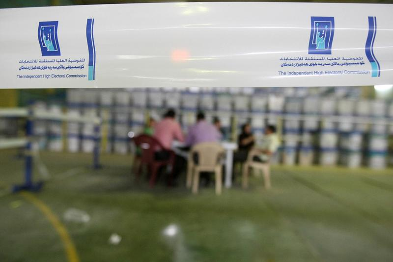Election officials at Iraq's Independent High Electoral Commission (IHEC) sort votes next to ballot boxes at their offices in Baghdad on March 17, 2010.