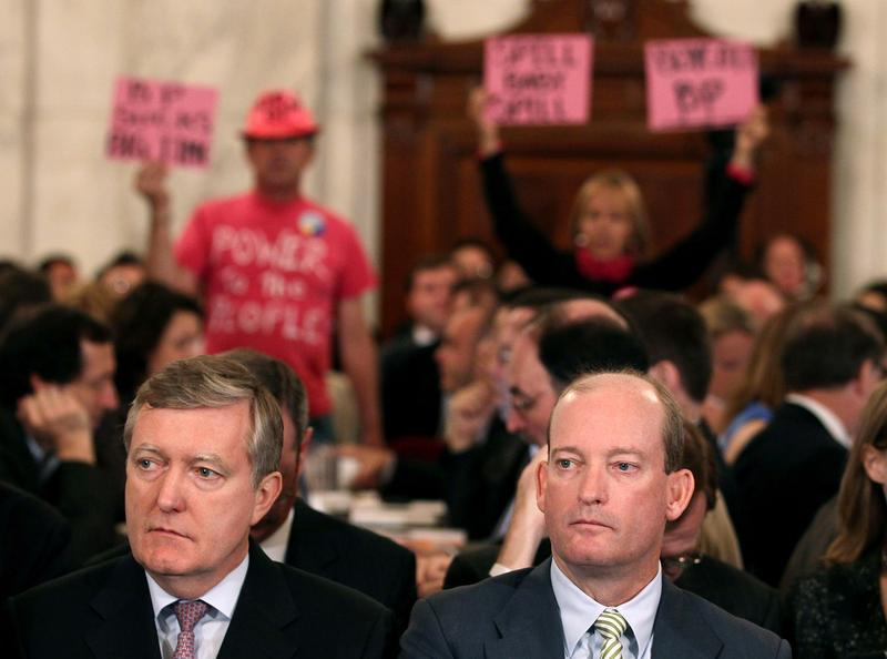 Lamar McKay (R), president and chairman of BP America Inc, and David Nagel (L), Executive Vice President of BP America,wait to testify as people protest behind them during a Senate hearing.