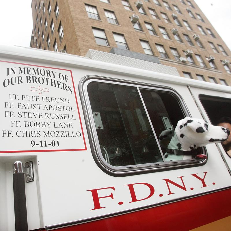 FDNY Engine 55 with an enscription honoring five firefighters killed on September 11, 2001, along with a doll dog in New York City.