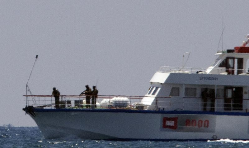 Armed soldiers stand on the bow of a boat as it enters the northern entrance of the port of Ashdod on May 31, 2010, following the storming by Israeli navy commandos of an aid flotilla bound for Gaza.
