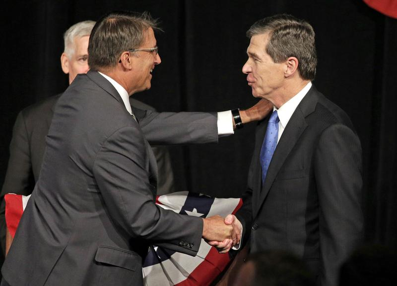 North Carolina Gov. Pat McCrory, left, shakes hands with North Carolina Attorney General Roy Cooper, right, after a candidate forum in Charlotte, N.C., Friday, June 24, 2016.