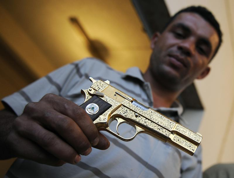 Libyan National Transitional Council (NTC) fighter Nabil Ali Dagouich holds Qaddafi's golden gun after participating in his capture a day before. Oct. 21, 2011