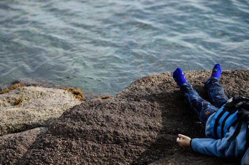 The body of a child lies by the beach in Canakkale's Bademli district on January 30, 2016 after at least 33 migrants drowned when their boat sank in the Aegean Sea while trying to cross from Turkey.