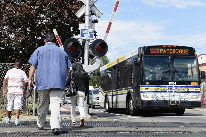 A bus carries individuals through the suburban village of Patchogue on Long Island, New York