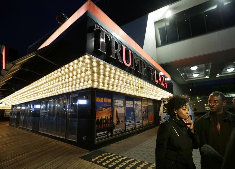 A card dealer and her friend stand outside the Trump Plaza Hotel and Casino in Atlantic City, which shut down in 2014.