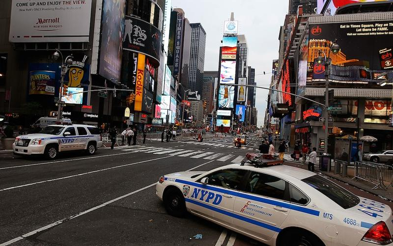 Police cruisers stand by at sunrise at the scene where a crude car bomb had been parked at 45th Street and 7th Avenue in Times Square May 2, 2010 in New York, New York.