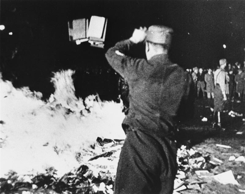 "A member of the SA throws confiscated books into the bonfire during the public burning of ""un-German"" books in Berlin, May 10, 1933."