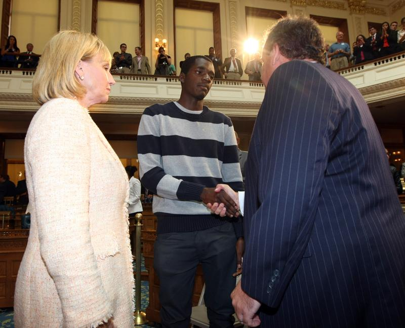 Gov. Chris Christie and Lt. Gov. Kim Guadagno talk to Iquan Small, who spent four months in jail on charges that were later dropped because he couldn't post the $2,000 cash bond needed to make bail.