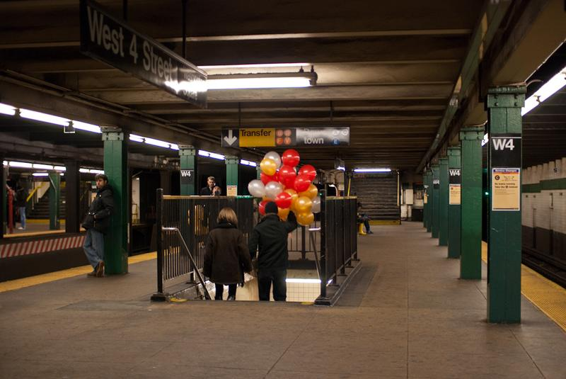 A couple holds hands, and balloons, on the NYC subway.