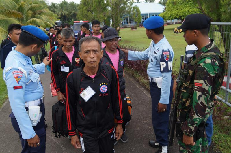 Indonesian soldiers check a group of 69 rescued Thai fishermen before boarding a Thai military plane in Ambon airport in Maluku province on April 9, 2015 during their repatriation.