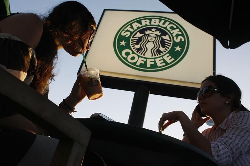 Customers relax and drink their beverages at a Starbucks Coffee shop on January 28, 2009 in Miami, Florida.