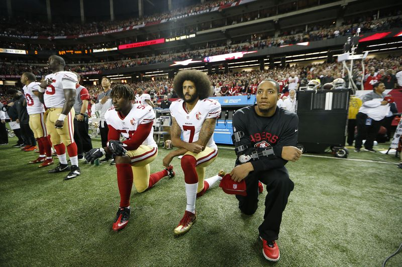 San Francisco 49ers quarterback Colin Kaepernick (center) kneelsv during the playing of the national anthem before a game on Sunday, Dec. 18, 2016, in Atlanta.