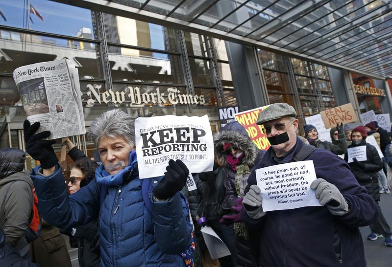 Protesters hold signs and a copy of the New York Times during a rally in front of The New York Times building in New York City on Sunday, Feb. 26, 2017.
