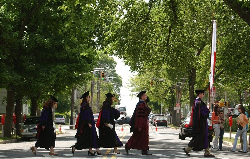 Faculty and students in academic robes walk across a street on the campus of Rutgers University in New Brunswick, N.J., during commencement exercises Wednesday, May 18, 2005.