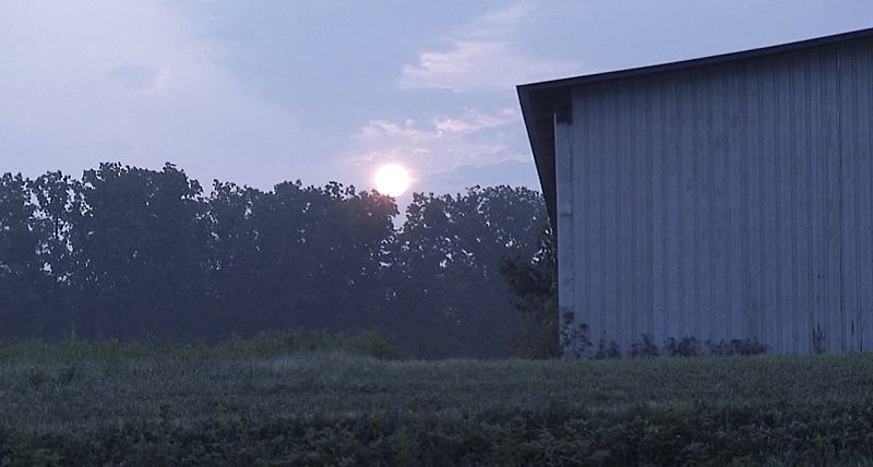 The sun rises over a tobacco field and barn at fourth-generation tobacco farmer Chris Haskins' farm in Chatham, Va.