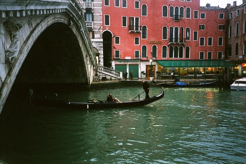 A gondola plies the waters of the Grand Canal, heading under the Ponte del Rialto, free of summer's heavy tourist traffic.