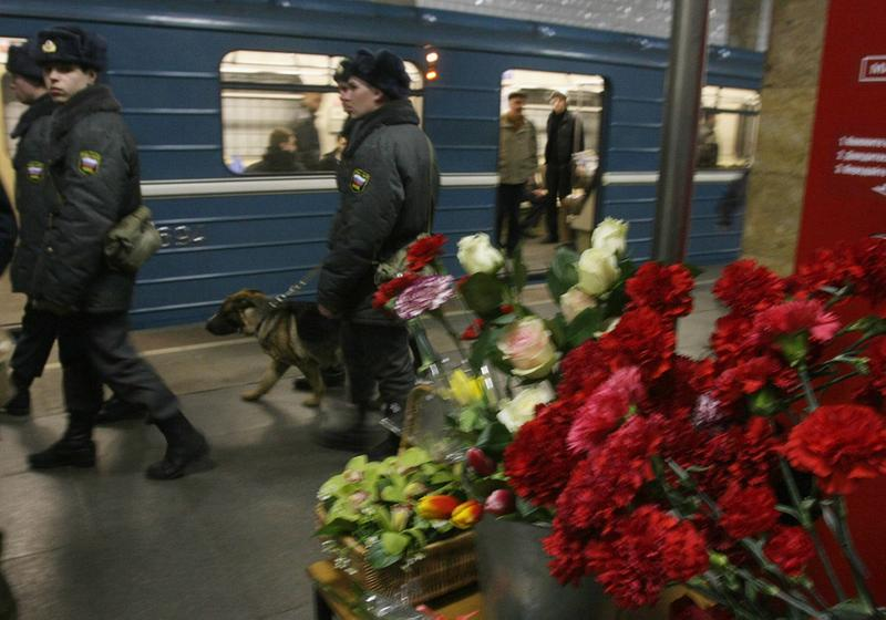 Russian police patrol near flowers left in memory of the victims of a blast at the Park Kultury metro station in Moscow on March 29, 2010.