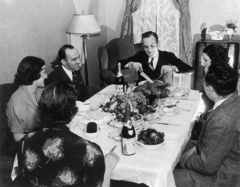 A family sits down to Thanksgiving dinner, circa 1935.