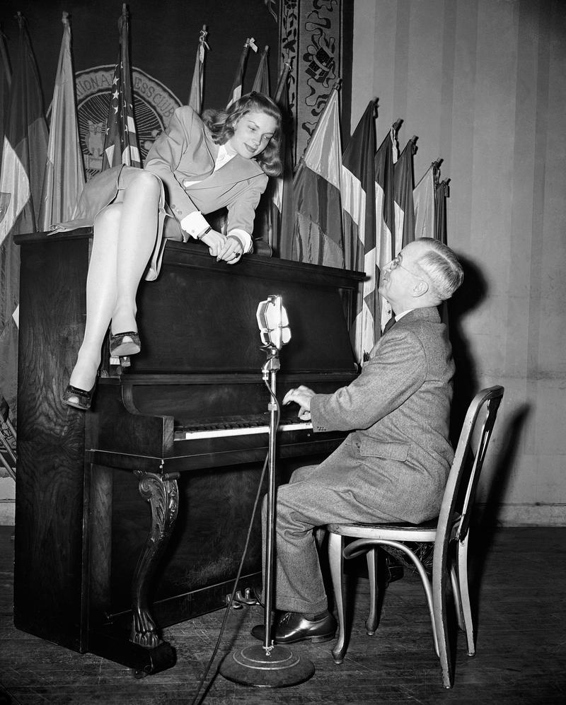 In this Feb. 10, 1945 file photo, Vice President Harry S. Truman plays the piano as actress Lauren Bacall lies on top of it during her appearance at the National Press Club canteen in Washington.