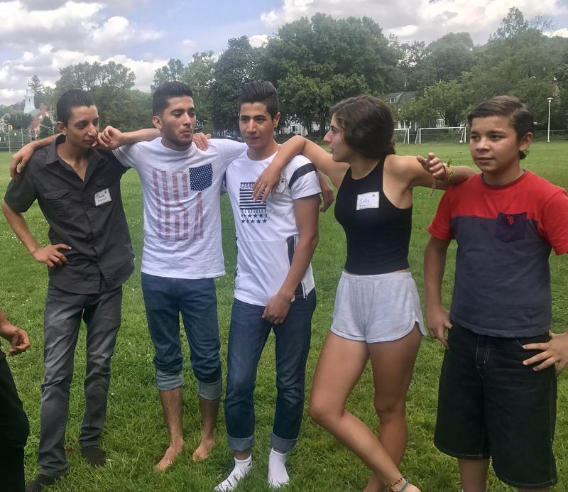 Syrian and American teens gather together on a field in summer 2017.