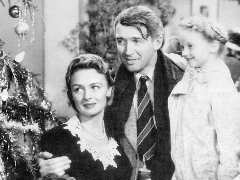 A screenshot of Jimmy Stewart, Donna Reed and Karolyn Grimes in the film 'It's a Wonderful Life.'