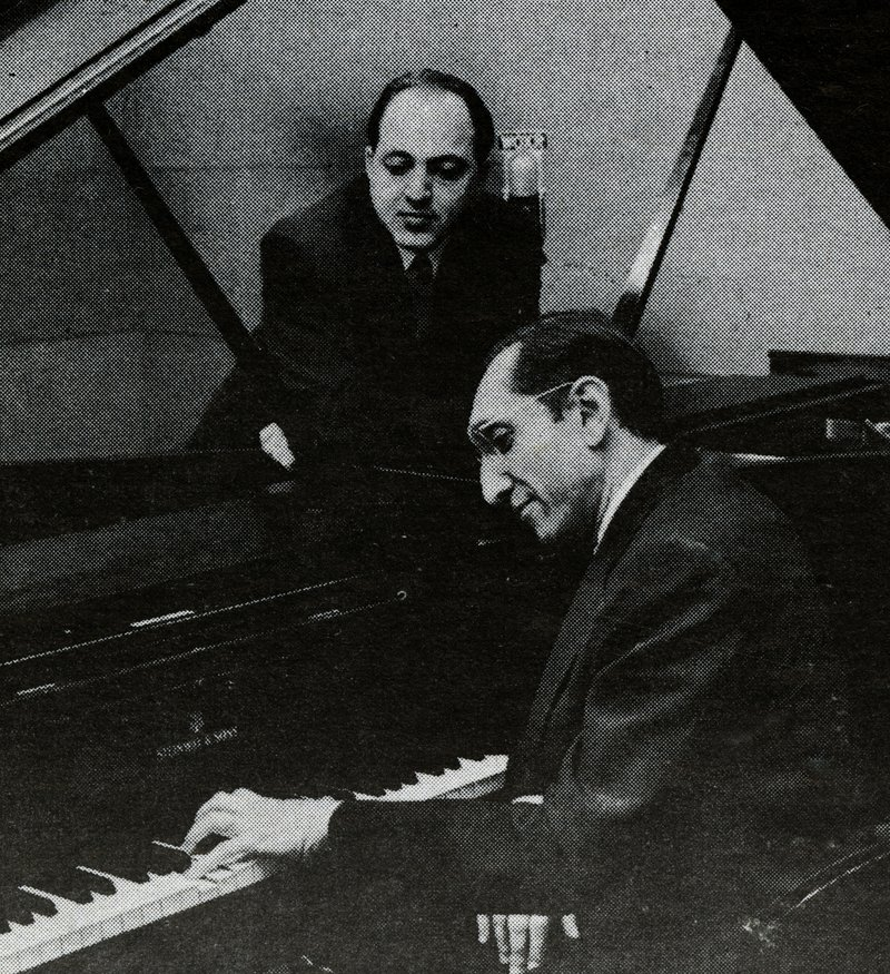 Leonid Hambro standing and Jascha Zayde seated at the piano as they go over a new duo piano arrangement at WQXR.