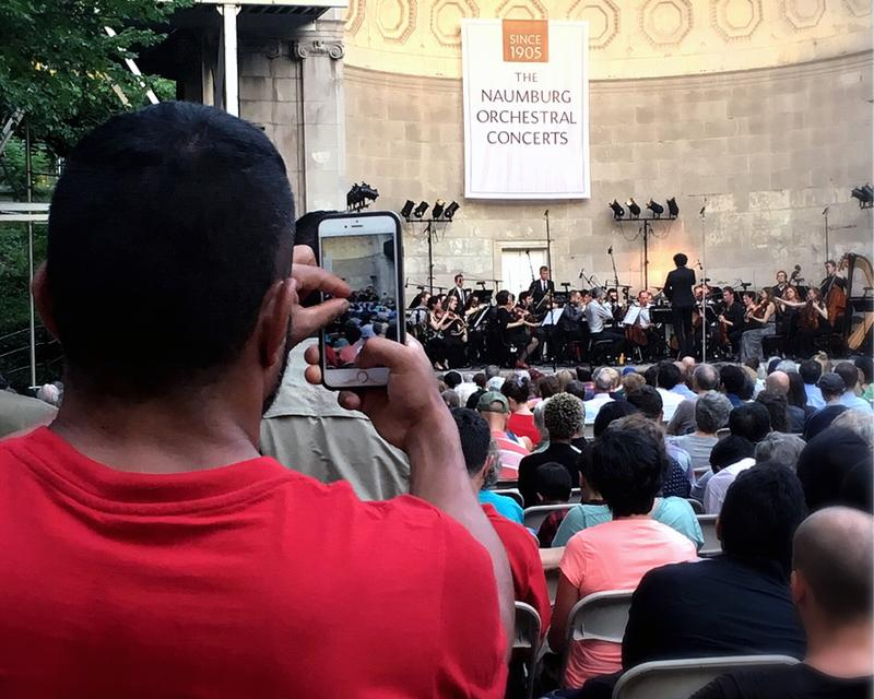 An audience member snaps a photo of The Knights at the Naumburg Bandshell.