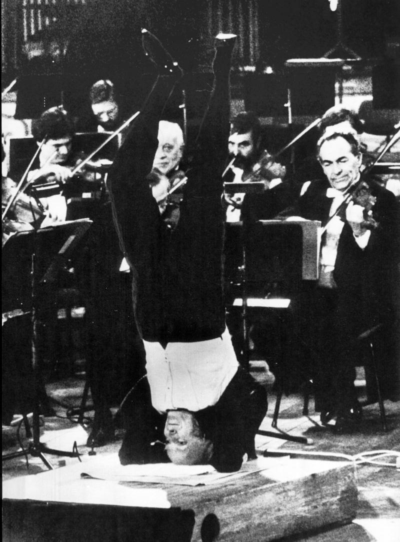 Violinist Yehudi Menuhin stands on his head in a yoga position as he conducts with his feet the Berlin Philharmonic