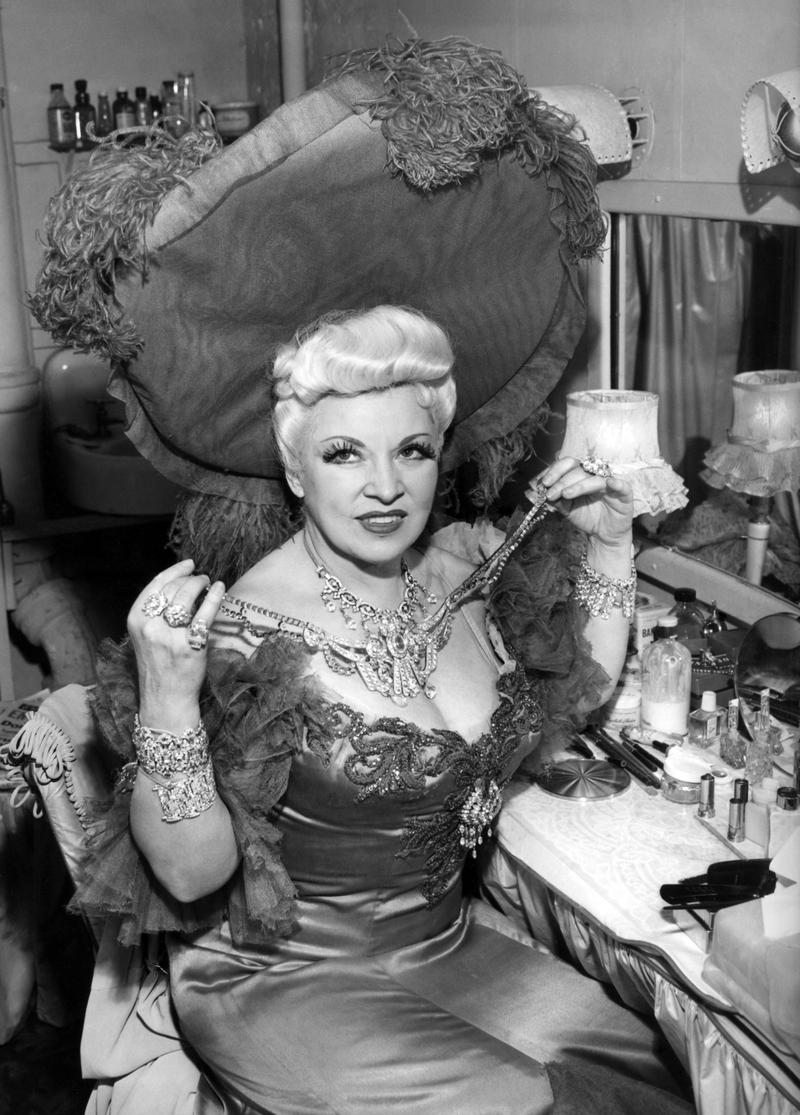 "Just before curtain call, Mae West puts on the ""prop"" diamonds which she wears in Diamond Lil, in her dressing room at the Plymouth Theatre in New York on Dec. 15, 1949. The props are given a value of"