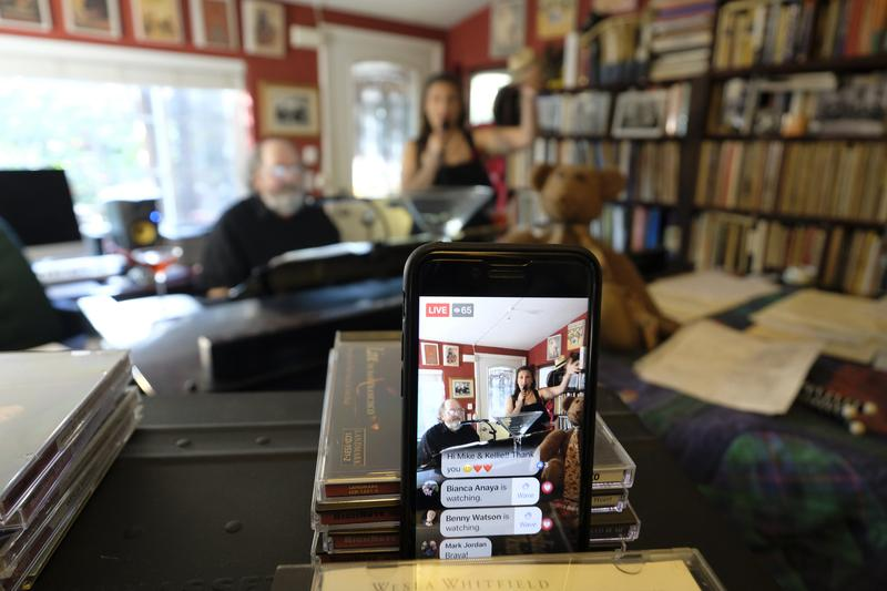 "A smartphone broadcasts on Facebook Live pianist, composer and arranger Mike Greensill joining vocalist Kellie Fuller for a ""virtual cocktail party piano bar"" Thursday, March 19, 2020, in St. Helena"