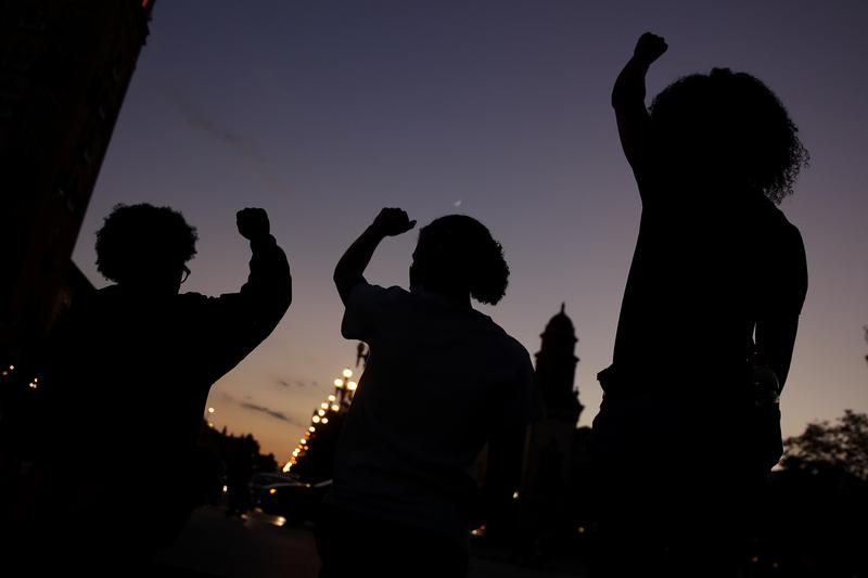 People raise their fists Tuesday, June 23, 2020, in Kansas City, Mo., during a protest over the death of Black people at the hands of police.