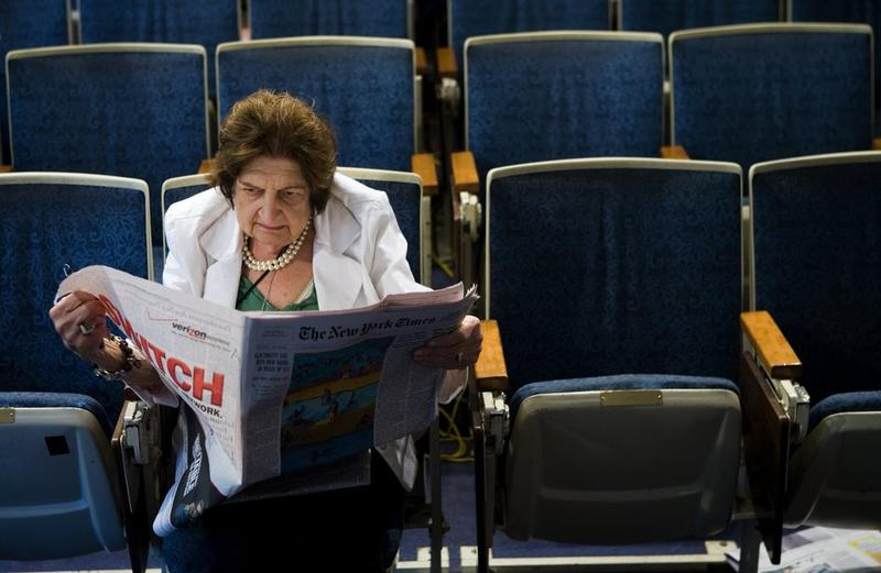 (FILE PHOTO) Senior White House Correspondent Helen Thomas reads the newspaper while sitting in her chair in the White House press room August 2, 2006 in Washington, DC.