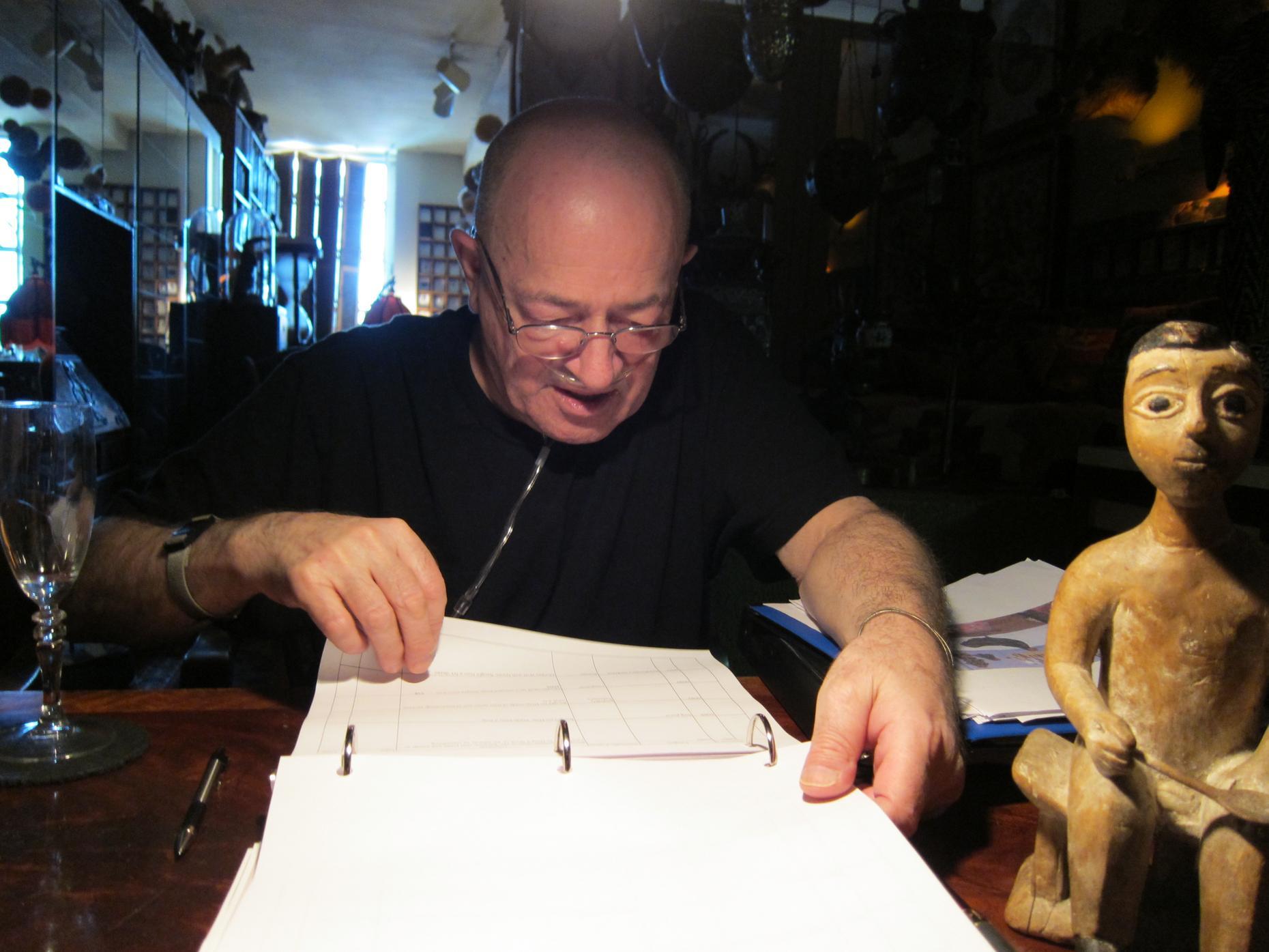 Barton cataloging items in his apartment