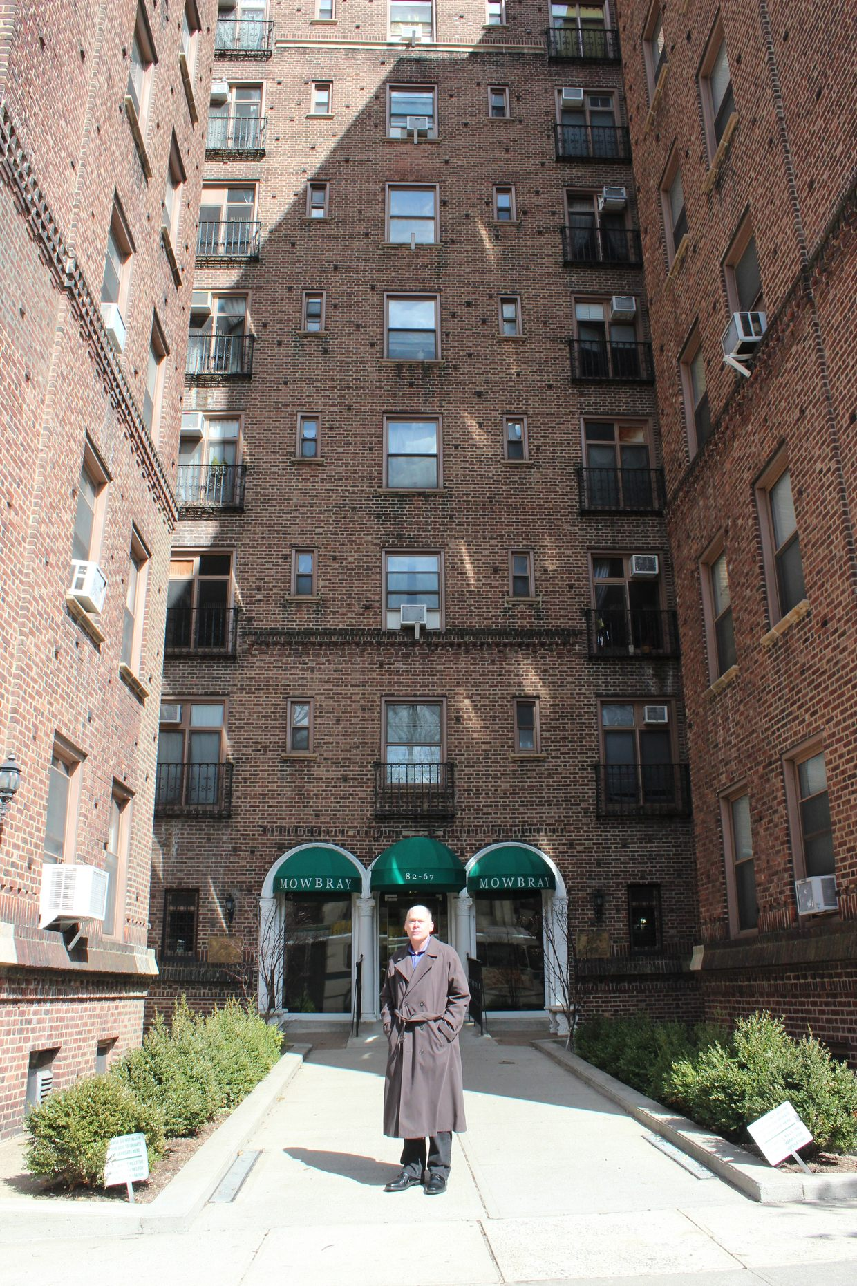 Author Kevin Cook stands outside the Mowbray Apartment building, across the street from where Kitty Genovese was attacked.