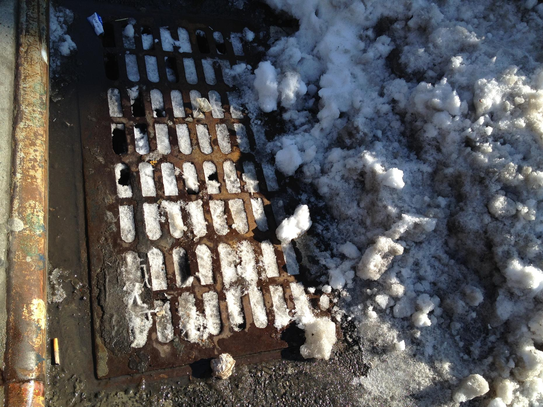 Street grate clogged with snow