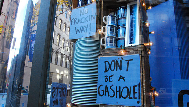 "Each of the store's windows at 19th St. and Broadway features colorful protest signs bearing slogans like: ""GIFTS for the 99%,"" ""NO FRACKIN WAY!"" and ""SHOP LOCAL EAT LOCAL SUPPORT LOCAL CAUSES!"""
