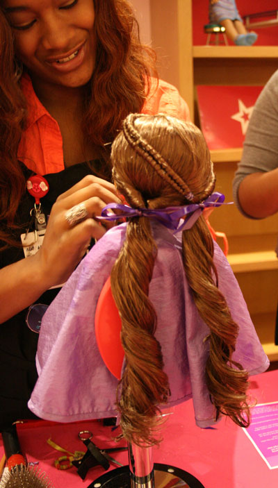 American Girl workers comb and braid customers' dolls' hair.