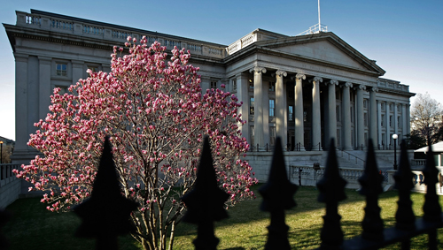Spring-time flowers bloom on a tree in front of the U.S. Treasury Department building. (Chip Somodevilla/Getty Images)