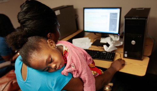 Unemployed mother Janet Francis of Brooklyn (in blue) looks for a job while her daughter Kayli, 2, sleeps on her shoulder at the New York State Labor Department's Division of Employment Services resource room July 2, 2009. (Getty)