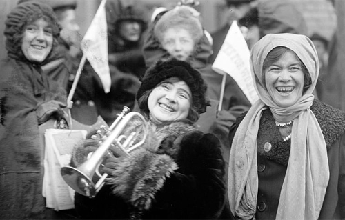 Suffragists rally, February 1913, waving pennants reading Votes for Women.